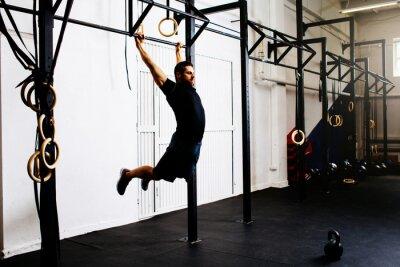 Naklejka Mężczyzna na siłowni ćwiczenia kipping pull-up