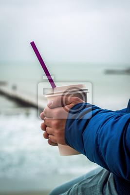 Naklejka Mężczyzna rozgrzewa dłonie z filiżanką kawy na wynos. Morze jest w tle.