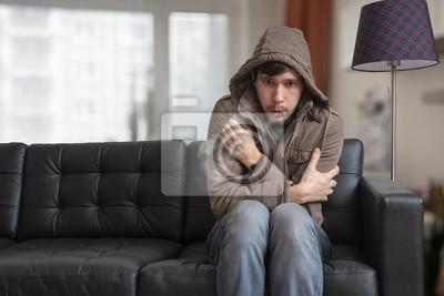 Naklejka Mężczyzna siedzi na kanapie w domu i zimno.