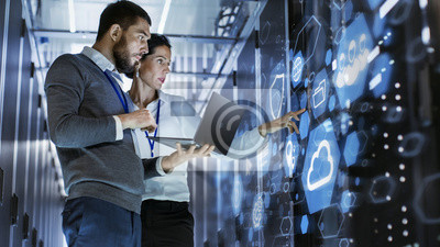 Naklejka Mężczyzna Specjalista IT trzyma laptopa i omawia pracę z techniką serwera kobiece. Stoją w Data Center, szafie serwerowej Rack z ikoną i wizualizacją Cloud Server.