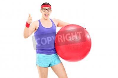 Naklejka Mężczyzna sportowiec gospodarstwa pilates piłkę i daje kciuk w górę na białym tle