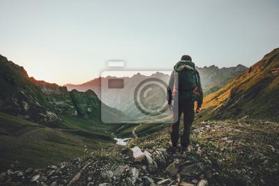 Naklejka Mężczyzna wycieczkuje przy zmierzch górami z ciężkim plecaka podróży stylu życia podróży wanderlust przygody wakacjami plenerowy samotnie w dzikiego