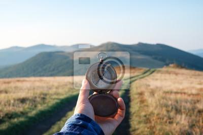 Naklejka Mężczyzna z kompasem w ręce na góry drodze. Koncepcja podróży. Fotografia krajobrazowa