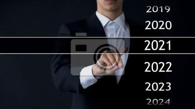 Naklejka Mężczyzna znajduje 2021 rok w wirtualnym archiwum, zbiorze statystyk, raportach rocznych