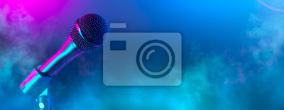 Naklejka Microphone on stage close-up. Mic closeup. Karaoke, night club, bar. Music concert. Mike over colorful lights background. Song, music concept wide backdrop, border art design