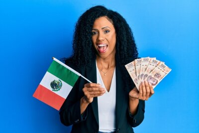 Naklejka Middle age african american woman holding mexico flag and mexican pesos banknotes celebrating crazy and amazed for success with open eyes screaming excited.