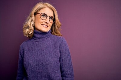 Naklejka Middle age beautiful blonde woman wearing casual purple turtleneck sweater and glasses looking away to side with smile on face, natural expression. Laughing confident.