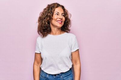 Naklejka Middle age beautiful woman wearing casual t-shirt standing over isolated pink background looking to side, relax profile pose with natural face and confident smile.