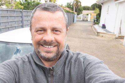 Naklejka middle aged man handsome make selfie in home alley garden guy happy with smartphone