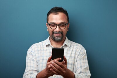 Naklejka Middle aged man of Indian origin looking at his mobile phone with a surprise