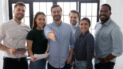 Naklejka Millennial male leader stretch out his hand for handshake welcoming new employee invites newcomer to corporate team, group showing amity, human resources, boss greets clients express respect concept
