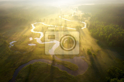 Naklejka Misty morning river in sunlight. River landscape aerial view. Riverside view from above. Summer nature in sun rays. Drone view on  sunny nature. Scenery river top view.