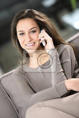Młoda atrakcyjna kobieta rozmawia przez telefon w domu