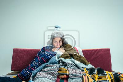 Naklejka Młoda chora kobieta z kominem siedzi na kanapie w domu lub studio pokryte dzianiny ciepłe ubrania. Choroba, grypa, koncepcja bólu. Relaks w domu. Koncepcje opieki zdrowotnej.