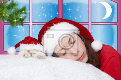 Młoda dziewczyna i mały kot ma na sobie Santa kapelusz spania