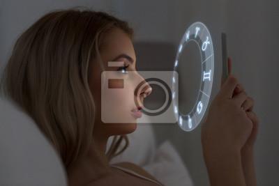 Naklejka Młoda kobieta czyta horoskop na smartfonie