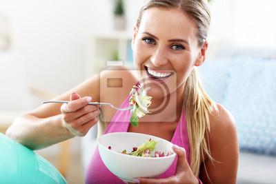 Naklejka Młoda kobieta jedzenie zdrowe sałatki po treningu
