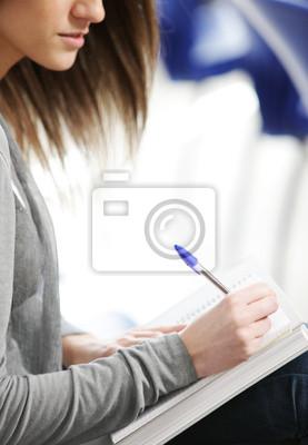 Młoda kobieta jest pisanie notatek