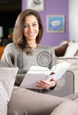 Naklejka młoda kobieta, leżąc na kanapie z książką