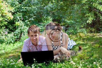 Młoda kobieta, mężczyzna i kot leżący z laptopem w parku