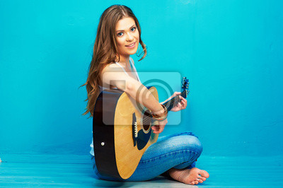 Naklejka Młoda kobieta muzyk z gitara siedzi na podłodze.