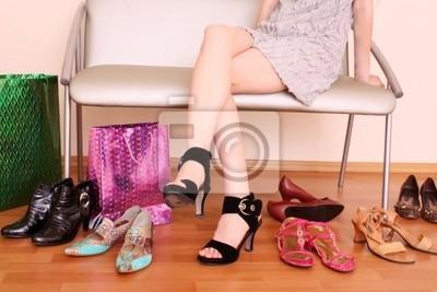 Naklejka Młoda kobieta próby na nowe buty w sklepie.