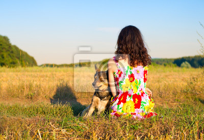 Młoda kobieta siedzi z psem na łące o zachodzie słońca