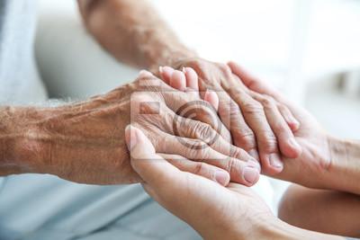 Naklejka Młoda kobieta trzyma starszego mężczyzna ręki, zbliżenie