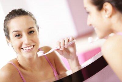 młoda kobieta w łazience czyszczenia zębów