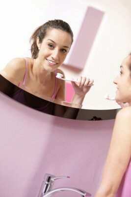 młoda kobieta w łazience czyszczenia zęby