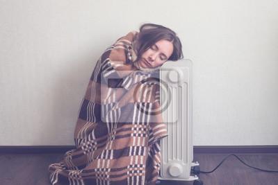 Naklejka Młoda kobieta w wełnianej kratę rozgrzewkę rąk nad grzałką elektryczną