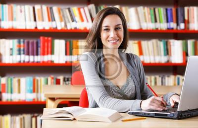 Młoda kobieta z jego komputerze w bibliotece.