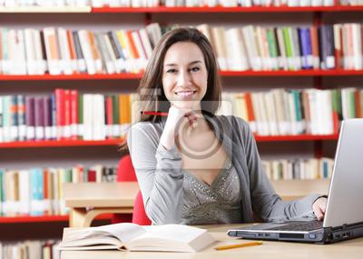 Naklejka Młoda kobieta z jego laptopa w bibliotece.