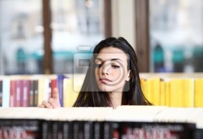 młoda, ładna kobieta, patrząc na książki w księgarni