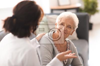 Naklejka Młoda lekarka odwiedza starszej kobiety w domu