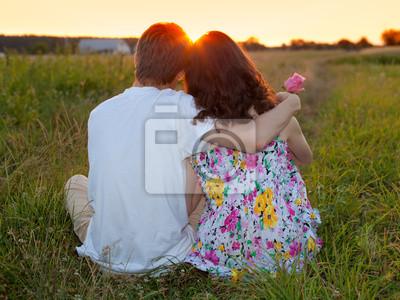 Młoda para siedzi z powrotem na trawę i patrząc na zachód słońca