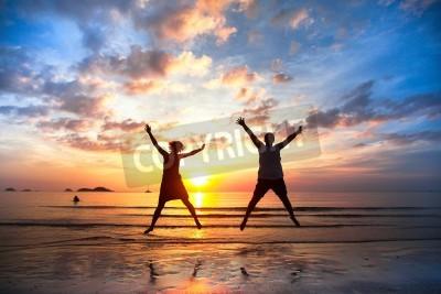 Naklejka Młoda para w skoku na plaży morza na zachodzie słońca Concept długo oczekiwany urlop