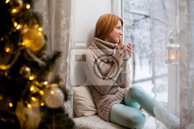 Naklejka Młoda piękna kobieta z czerwonawego włosy siedzi w domu przy oknie z kubkiem gorącej kawy na sobie dzianiny ciepły sweter. Choinka z dekoracjami i światła w pokoju, śnieżna zima na zewnątrz