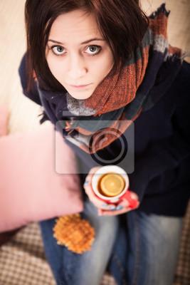 Naklejka Młoda piękna kobieta z czerwonawego włosy siedzi w domu przy oknie z kubkiem gorącej kawy noszenie dzianiny ciepły sweter
