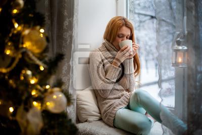Naklejka Młoda piękna kobieta z czerwonawego włosy siedzi w domu przy oknie z kubkiem gorącej kawy noszenie dzianiny ciepły sweter. Choinka z dekoracjami i światła w pokoju, śnieżna zima na zewnątrz