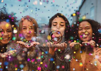 Naklejka Młode kobiety dmuchanie konfetti z rąk. Przyjaciele świętują wieczorem na tarasie.