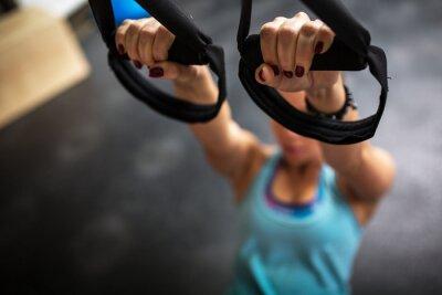 Naklejka Młode samice na siłowni pracuje na jej brzucha na TRX
