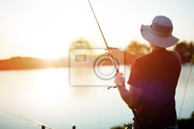 Naklejka Młodego człowieka połów na jeziorze przy zmierzchem i cieszyć się hobby