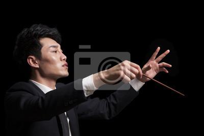 Naklejka Młody dyrygent z batutą podniósł, czarnym tle
