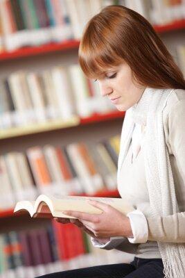 Młody student czytanie w bibliotece