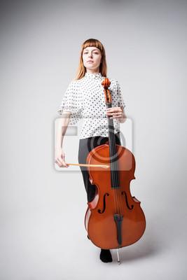 Naklejka Młody wiolonczelista stoi i gra na wiolonczeli