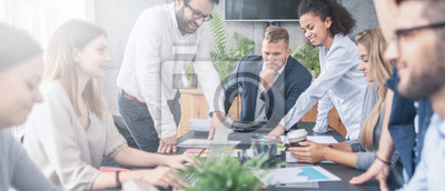 Naklejka Młodzi kreatywnie ludzie biznesu spotyka przy biurem.