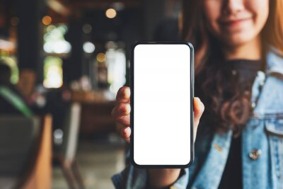 Naklejka Mockup image of a woman holding and showing black mobile phone with blank white screen in cafe