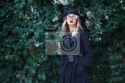 Moda bliska portret stylowe m? Odych blond kobieta z czerwonymi ustami, modne okulary i skórzane czarny kapelusz w liściach winogron. Jesienny modny wygląd. Koncepcja wysokiej mody.