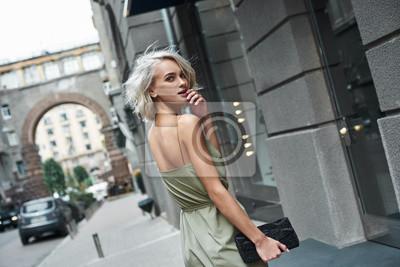 Naklejka Moda. Młoda stylowa kobieta spaceru na ulicy miasta patrząc wstecz aparat uśmiecha się figlarny